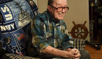 In this November 2014 photo, Lawrence J. Reilly Sr., a U.S. Navy veteran of World War ll and the Vietnam War, sits in the living room of his home in Syracuse, N.Y. He and his 20-year-old son Lawrence J. Reilly Jr. were serving together on U.S. Navy destroyer Frank E. Evans when the ship was cut in half in a collision with the aircraft carrier HMAS Melbourne of the Royal Australian Navy during joint maneuvers in the South China Sea. Seventy-four sailors died but the Pentagon has rejected a longstanding request from survivors of the disaster to add the names of their fallen comrades to the Vietnam Veterans Memorial in Washington, D.C., saying the accident occurred outside the Vietnam combat zone. (Mike Greenlar/Syracuse Post-Standard via AP)