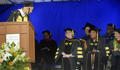 2017 Smith College Senior Class President, Badriyyah Salem Alsabah, left, jokes with Oprah Winfrey, seated center, during Smith College's 139th Commencement ceremony on Sunday, May 21, 2017 in Northampton, Mass. The author, actress, philanthropist and former talk show host gave the college's commencement address. (David Molnar/Springfield Republican via AP)