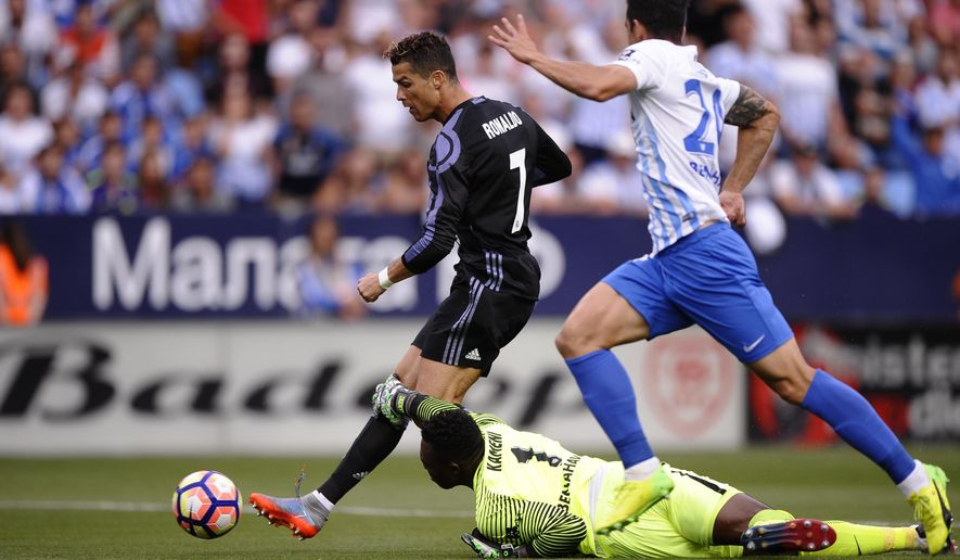 Real Madrid's Cristiano Ronaldo scores the opening goal during a Spanish La Liga soccer match between Malaga and Real Madrid in Malaga, Spain, Sunday, May 21, 2017. (AP Photo/Daniel Tejedor)