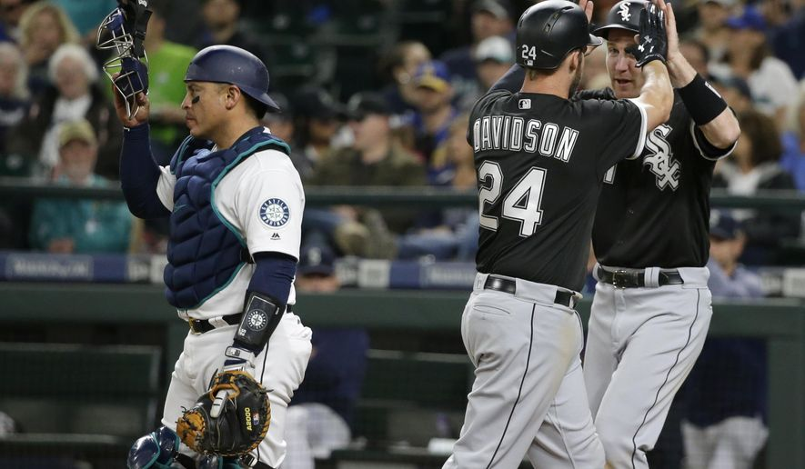 Chicago White Sox's Matt Davidson (24) is greeted by Todd Frazier, right, as Seattle Mariners catcher Carlos Ruiz, left, looks on after Frazier scored on a home run hit by Davidson in the seventh inning of a baseball game, Saturday, May 20, 2017, in Seattle. (AP Photo/Ted S. Warren)