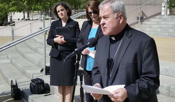 """St. Louis Archbishop Robert Carlson speaks at a news conference Monday, May 22, 2017, announcing a federal lawsuit to stop a St. Louis ordinance that prohibits discrimination based on """"reproductive health decisions."""" The suit says the law enacted in February infringes on freedom of religion rights of those who oppose abortion. Behind Carlson are attorney Sarah Pitlyk, left, of the Thomas More Society, a non-profit law firm that filed the suit, and Peggy Forrest, executive director of Our Lady's Inn, which provides services for pregnant women who are homeless and is a plaintiff in the lawsuit. (AP Photo/Jim Salter) **FILE**"""