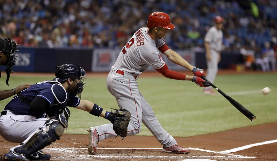 Los Angeles Angels' Andrelton Simmons (2) hits an RBI sacrifice fly off Tampa Bay Rays starting pitcher Jake Odorizzi during the first inning of a baseball game, Monday, May 22, 2017, in St. Petersburg, Fla. Angels' Cameron Maybin scored. Catching for the Rays is Derek Norris. (AP Photo/Chris O'Meara)