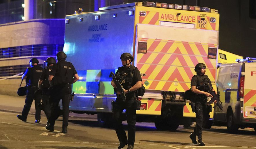 Armed police work at Manchester Arena after reports of an explosion at the venue during an Ariana Grande gig in Manchester, England Monday, May 22, 2017. Several people have died following reports of an explosion Monday night at an Ariana Grande concert in northern England, police said. A representative said the singer was not injured. (Peter Byrne/PA via AP)