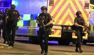 Armed police respond after reports of an explosion at Manchester Arena during an Ariana Grande concert in Manchester, England, Monday, May 22, 2017. Several people have died following reports of an explosion Monday night at the concert in northern England, police said. A representative said the singer was not injured. (Peter Byrne/PA via AP)