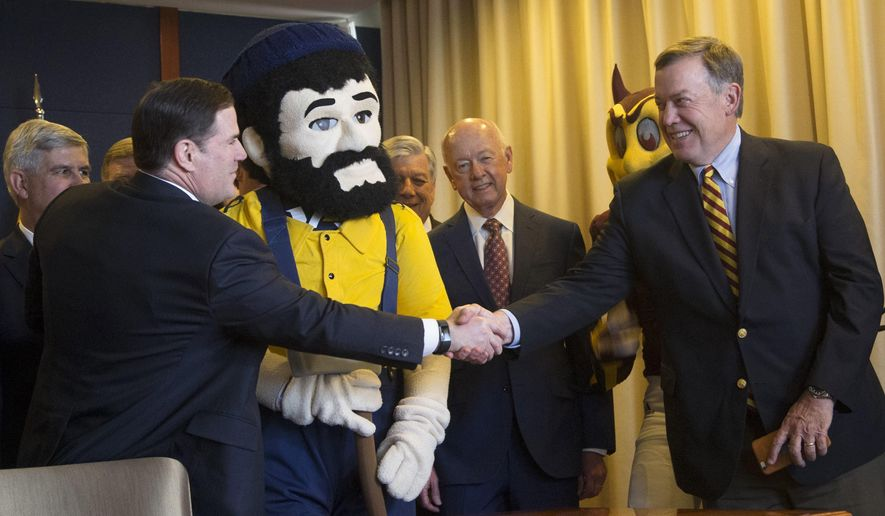Arizona Gov. Doug Ducey shakes hands with Arizona State University President Michael Crow during his signing of a $1 billion bonding authority for the state's public universities in the Governor's office in Phoenix, Ariz., Monday, May 22, 2017. Ducey on Monday signed legislation that allows the state's three public universities to borrow up to $1 billion and puts the state on the hook for $27 million a year to help cover the payments. (Patrick Breen/The Arizona Republic via AP)