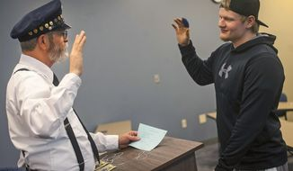 """In this April 27, 2017 photo, Heartland Community College adjunct instructor of general  studies Van Furrh, left, portrays an immigration officer as he gives an oath to student Alec Callender during """"Boxes and Walls: The Oppression Experience"""" at the Astroth Community Education Center in Normal, Ill. The exercise was """"about raising awareness of what some of their classmates may have gone through to get here,"""" explained Shamelle Grabill, a tutoring services facilitator at Heartland who helped design the immigration part of the program. (Lewis Marien/The News-Gazette via AP )"""