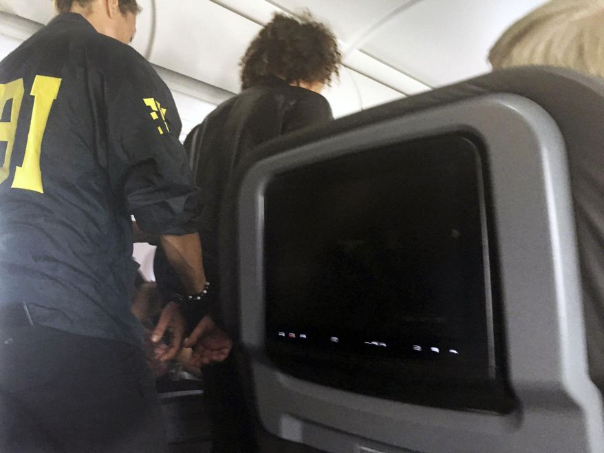 In this file photo provided by Donna Basden, a man is escorted off an American Airlines flight after it landed in Honolulu, Friday, May 19, 2017. Court records say the man who caused a disturbance on a flight from Los Angeles to Honolulu had no luggage other than a laptop and needed a wheelchair to board the plane because he appeared to be under the influence of drugs or alcohol. (Donna Basden via AP, File)