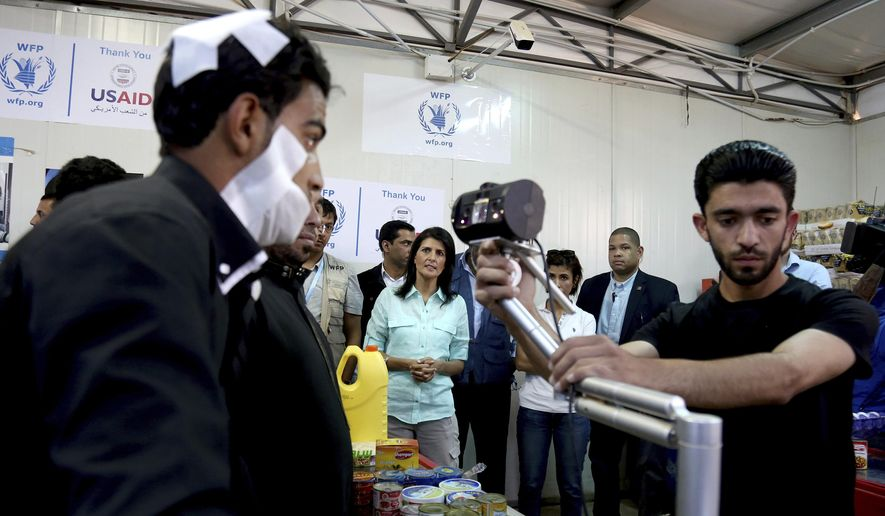 "U.S. Ambassador to the United Nations Nikki Haley, background center, looks on as a bandaged Syrian refugee has his iris scanned at a supermarket, Sunday, May 21, 2017 in Zaatari Refugee Camp,  Jordan. Haley said the Trump administration wants to step up help for the millions of displaced Syrians. Yet Haley's message is at odds with President Donald Trump's ""America First"" agenda, his planned budget cuts and his hardline position on admitting refugees. (AP Photo/Raad Adayleh, Pool)"