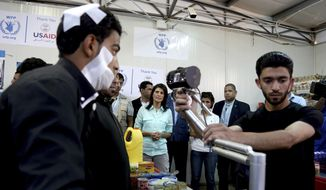 """U.S. Ambassador to the United Nations Nikki Haley, background center, looks on as a bandaged Syrian refugee has his iris scanned at a supermarket, Sunday, May 21, 2017 in Zaatari Refugee Camp,  Jordan. Haley said the Trump administration wants to step up help for the millions of displaced Syrians. Yet Haley's message is at odds with President Donald Trump's """"America First"""" agenda, his planned budget cuts and his hardline position on admitting refugees. (AP Photo/Raad Adayleh, Pool)"""