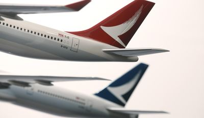 FILE - In this Jan. 28, 2016, file photo, two model jets of Hong Kong airline Cathay Dragon, formerly known as Dragonair, front, and Cathay Pacific Airways, are displayed at a news conference in Hong Kong. Hong Kong airline Cathay Pacific Airways said Monday, May 22, 2017 it's laying off nearly 600 staff at its headquarters as it faces rising competition from rival carriers and tough business conditions. (AP Photo/Kin Cheung, File)