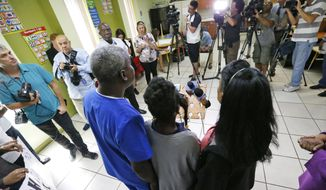 A Haitian family that did not want to be identified, living in the U.S. with Temporary Protected Status (TPS) speaks to members of the media, Monday, May 22, 2017, in Miami. The Trump administration is going to extend humanitarian protections for tens of thousands of Haitian immigrants who have been living in the United States since a deadly earthquake. Administration officials said the TPS for roughly 50,000 Haitians will expire in December. A final decision about the long-term fate of those immigrants will be decided at a later date. (AP Photo/Wilfredo Lee)