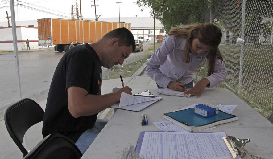 "In this April 28, 2017 photo, Aimee Gomez, a recruiter for ""maquiladora"" assembly plants in Reynosa, Mexico helps Juan Luis Alvarado de la Rosa fill out a job application in an industrial park, across the border from McAllen, Texas. President Donald Trump has said NAFTA was ""a catastrophic trade deal for the United States,"" but the reality is far more complicated, especially at the border where communities are enmeshed in a shared economy. (AP Photo/Christopher Sherman)"