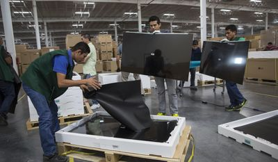 "In this March 23, 2017 photo, workers check screens for faults in Pantos logistics, a ""maquiladora"" LG flat screen television assembly plant in Reynosa, Mexico, across the border from McAllen, Texas. Many maquila workers making only $50 to $60 for a six-day work week rely on a few hours of daily overtime to make ends meet, according to Gilberto Lozoya, a maquila worker in Nuevo Laredo. (AP Photo/Rodrigo Abd)"