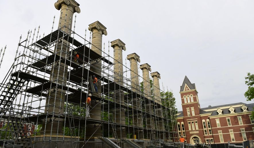 In this Wednesday, May 17, 2017 photo, workers assemble scaffolding around the columns on the Francis Quadrangle at the University of Missouri campus in Columbia, Mo. The six columns, which were built in 1842, have been battered by weather and students over the years. (Emil Lippe/Missourian via AP)