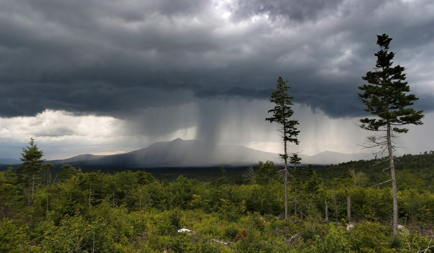 FILE - In this August 2015 file photo, a rain storm passes over Mt. Katahdin in this view from land that is now the Katahdin Woods and Waters National Monument in northern Maine. Motorists on Interstate 95 in Maine won't see signs directing them to the new national monument created by President Barack Obama because Gov. Paul LePage is refusing to let the state install them. (AP Photo/Robert F. Bukaty, file)