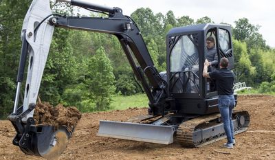 Energy Secretary Rick Perry operates and excavator that includes 3-D printed components at Oak Ridge National Laboratory's Manufacturing Demonstration Facility in Knoxville, Tenn., Monday, May 22, 2017. Perry said his goal is to protect jobs and funding for his agency and its research facilities. (AP Photo/Erik Schelzig)