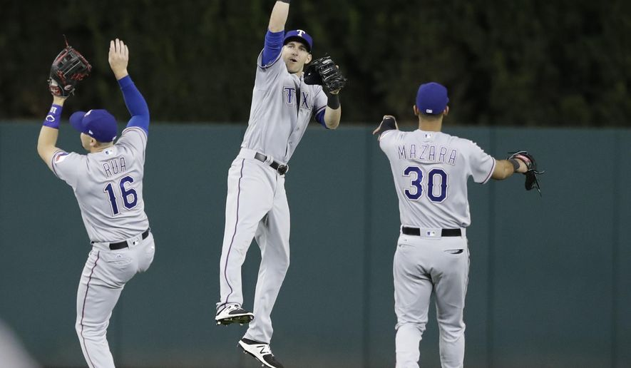 Texas Rangers left fielder Ryan Rua (16), center fielder Jared Hoying and right fielder Nomar Mazara (30) celebrate the team's 5-2 win over the Detroit Tigers in a baseball game, Sunday, May 21, 2017, in Detroit. (AP Photo/Carlos Osorio)