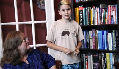 "In this May 3, 2017, photo, Ann Elder, of Friendswood, Texas, looks on at her son, Benjamin, as he is interviewed inside their home. Benjamin is an 11-year-old transgender boy. A bill that is likely to pass the Texas Legislature this month could force schools to reveal the identities of some transgender students. Elder said she would homeschool him to avoid ""having him humiliated every day in front of his classmates."" (AP Photo/John L. Mone)"