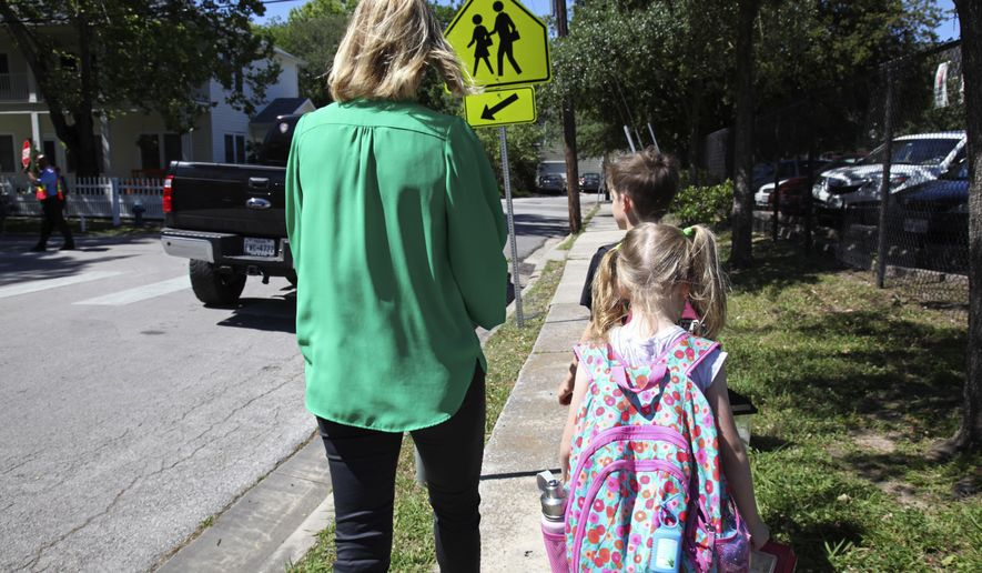 "In this May 4, 2017, photo Joanna Smith, of Houston, walks her twin first-graders home from school. One of her children is transgender and Smith fears the child's school would be compelled by the state to ""out"" her child's biological gender should a ""bathroom bill"" become law. (AP Photo/John L. Mone)"
