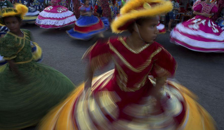 FILE - In this Feb.27, 2017, file photo, girls in costume dance during Maracatu Carnival celebrations in Nazare da Mata, Pernambuco state, Brazil. Despite the seeming abundance of riches for travelers, Brazil has a tourism problem. While you may have heard about the Amazon or the stunning beaches of Rio de Janeiro, you have probably also heard that Brazil has high crime, was swept by a Zika outbreak and that its politicians have concocted the largest graft scheme in Latin American history. (AP Photo/Eraldo Peres, File)