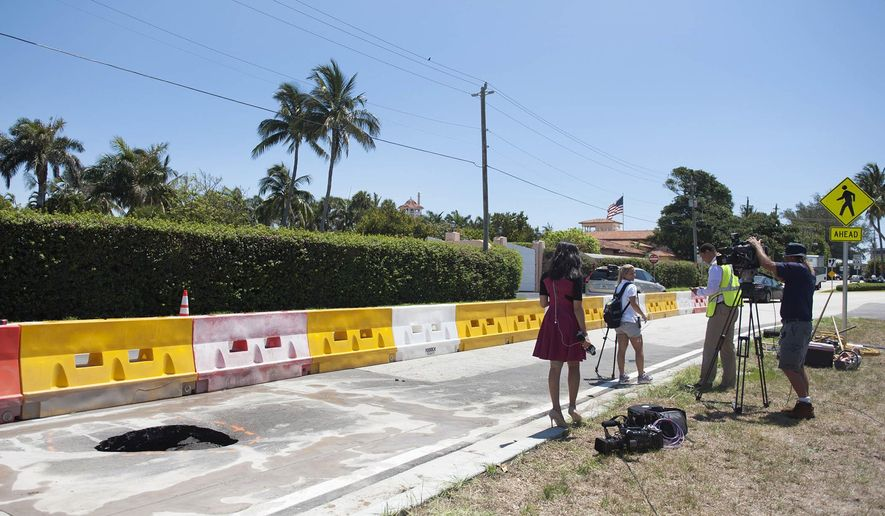 A TV crew reports next to a recently opened sinkhole near President Donald Trump's Mar-a-Lago estate, Monday, May 22, 2017 in Palm Beach, Fla. The 4-foot-by-4-foot hole was discovered Monday. It is near a new water drain and isn't a threat to the president's property. (Meghan McCarthy/Daily News via AP)