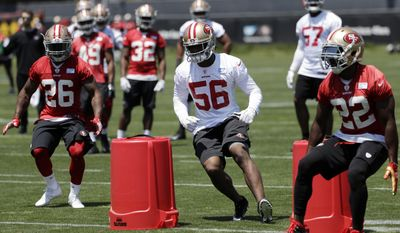 San Francisco 49ers players, from left, Kapri Bibbs (26) Reuben Foster (56) and Tim Hightower (22) go through drills during the team's organized team activity at its NFL football training facility Tuesday, May 23, 2017, in Santa Clara, Calif. (AP Photo/Marcio Jose Sanchez)