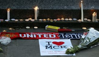 Candles and tributes were left after a vigil in Albert Square, Manchester, England, on Tuesday, the day after a suicide attack at an Ariana Grande concert attended by many young people. (Associated Press)