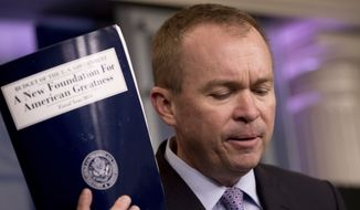 Budget Director Mick Mulvaney holds up a copy of President Trump's proposed fiscal 2018 federal budget as he speaks to members of the media at the White House on Tuesday. (Associated Press)