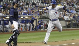 Toronto Blue Jays' Russell Martin scores past Milwaukee Brewers catcher Manny Pina during the second inning of a baseball game Tuesday, May 23, 2017, in Milwaukee. Martin scored on a ball hit by Joe Biagini. (AP Photo/Morry Gash)