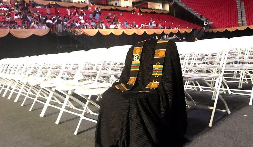 In the photo provided by Neal Augenstein, WTOP, Richard Collins III's graduation gown draped over front row chairs at Bowie State University ceremony, Tuesday, May 23, 2017, in College Park, Md. Collins, 23, who was visiting friends at the College Park campus, had just been commissioned as a second lieutenant in the U.S. Army and would have graduated from Bowie State, was stabbed and killed Saturday, May 20, 2017.   (Neal Augenstein/WTOP via AP)