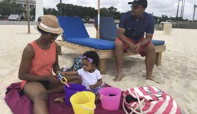 In this May 18, 2017 photograph, Kendra Winnick, left, enjoys the beach in Biloxi, Mississippi, with her husband, Alex Winnick, and their 1-year-old daughter, Alexa, on May 18, 2017. Kendra and Alex Winnick, who live in Meridian, Mississippi, said they don't have strong feelings about the Mississippi flag that contains the Confederate battle emblem, but Kendra Winnick said she knows the emblem is offensive to many older African-Americans. The mayor of Biloxi removed the state flag from display at city buildings because of the Confederate emblem that he said could make some residents and visitors feel unwelcome. (AP Photo / Emily Wagster Pettus)