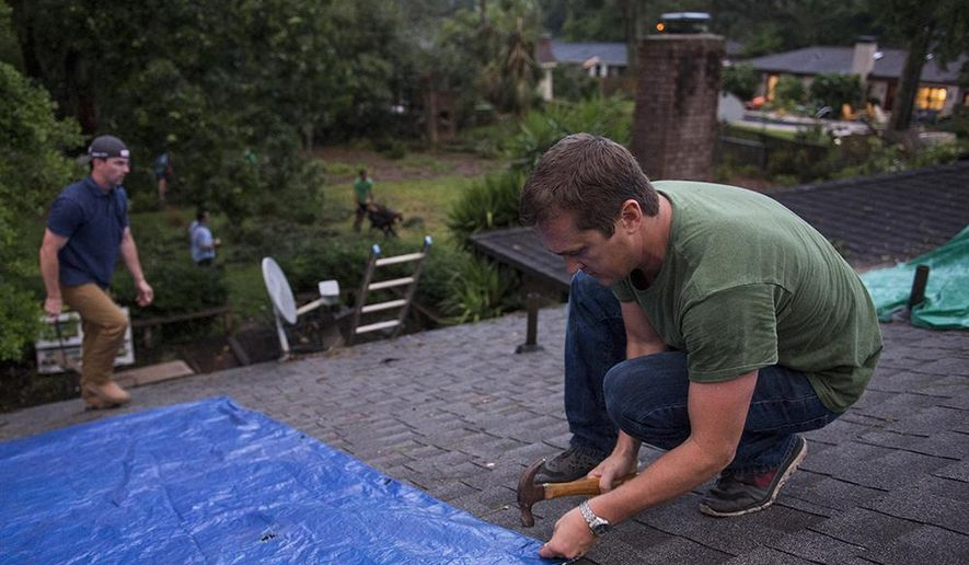 Hunter Saussy the IV hammers in nails to hold a tarp in place over a hole in his friend's roof on Wilmington Island, Ga., after a severe storm passed through the area causing heavy damage to several houses Tuesday evening, May 23, 2017. The threat of flooding continues across several southern states as heavy rain soaked the area and prompted new flood watches in the Carolinas while a massive storm system swept eastward. (Josh Galemore/Savannah Morning News via AP)