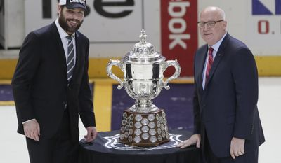 NHL Deputy Commissioner Bill Daly, right, presents injured Nashville Predators captain Mike Fisher with the Clarence S. Campbell Bowl after the Predators beat the Anaheim Ducks in Game 6 of the Western Conference final in the NHL hockey Stanley Cup playoffs Monday, May 22, 2017, in Nashville, Tenn. The Predators won 6-3 to win the series 4-2 and advance to the Stanley Cup Finals. (AP Photo/Mark Humphrey)