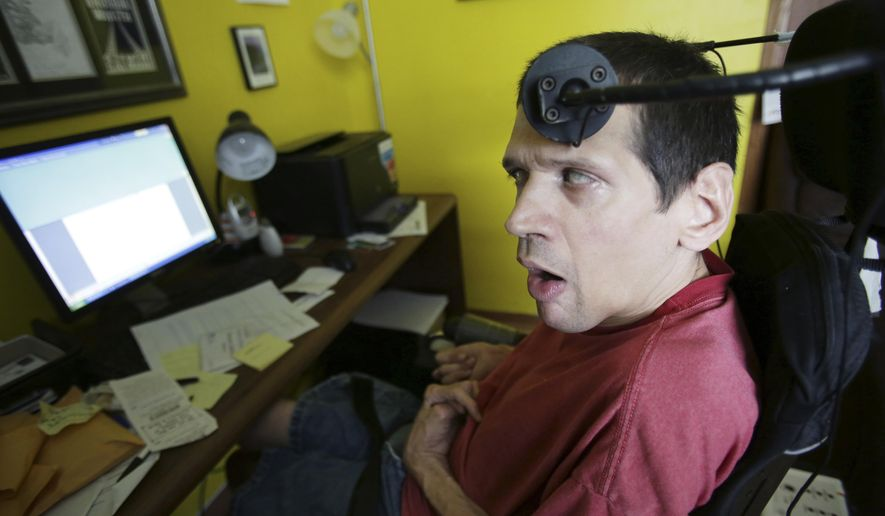 This photo taken April 12, 2017, shows Steven Salmon, a self-published author who is living with cerebral palsy, working on a new book using a device that is attached to his wheelchair that translates morse code to English that he activates by moving his head to the left or to the right, in his office at a group home where he lives in Madison, Wis. (Amber Arnold/Wisconsin State Journal via AP)