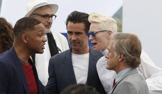 Actors Will Smith, left, Collin Farrell, Christopher Waltz talk after actors and directors from former Cannes selections posed for photographers during the photo call for the 70th Anniversary of the international film festival, Cannes, southern France, Tuesday, May 23, 2017. (AP Photo/Thibault Camus)