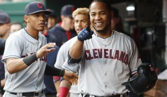 Cleveland Indians' Edwin Encarnacion celebrates in the dugout after hitting a two-run home run off Cincinnati Reds starting pitcher Amir Garrett in the third inning of a baseball game, Tuesday, May 23, 2017, in Cincinnati. (AP Photo/John Minchillo)