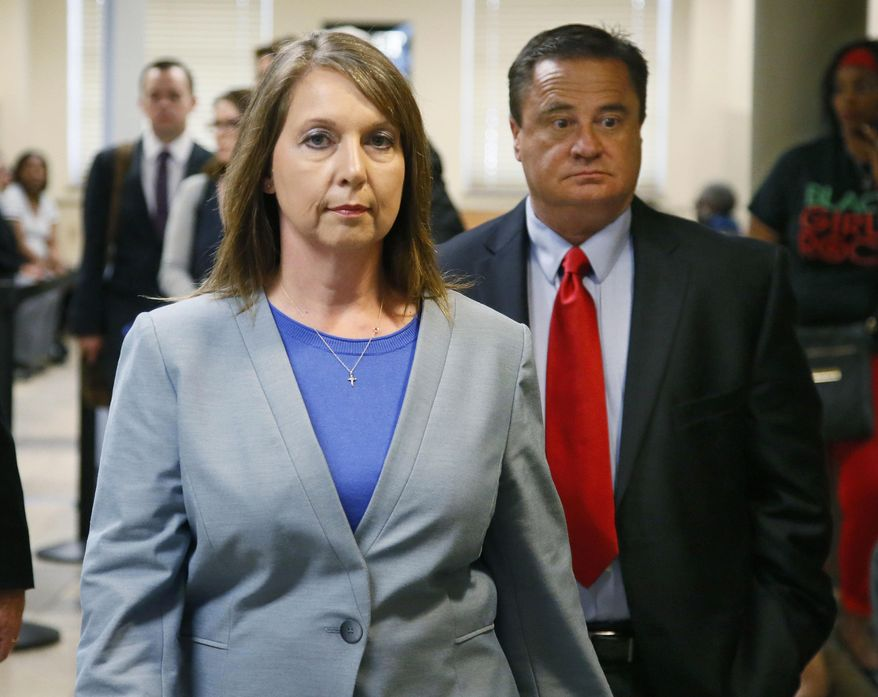 """FILE - In this May 17, 2017, file photo, Betty Shelby leaves the courtroom with her husband, Dave Shelby, right, after the jury in her case began deliberations in Tulsa, Okla. Shelby, who fatally shot an unarmed black man last year, was found not guilty of first-degree manslaughter. Shelby's attorney said Tuesday, May 23, 2017, that Shelby is back on the force working in an """"administrative"""" role, but declined to specify what job out of concern for the officer's safety. (AP Photo/Sue Ogrocki, File)"""