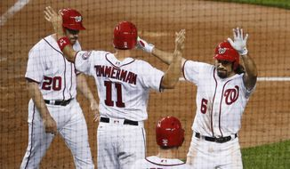 Washington Nationals Anthony Rendon (6) is congratulated by his teammates after hitting a three-run home run with Ryan Zimmerman (11) and Daniel Murphy (20), scoring during the fourth inning of a baseball game against the Seattle Mariners in Washington, Tuesday, May 23, 2017. Matt Wieters (32) is on deck. (AP Photo/Manuel Balce Ceneta)