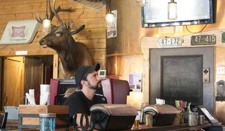 In this Thursday, May 18, 2017 photo, Adam Maleski waits to begin his shift in the kitchen a tavern in White Sulfur Springs, Mont. Maleski hasn't decided whether he will cast a ballot in the May 25 special election to fill Montana's vacant U.S. House seat. He has no health insurance, he said, because he can't afford it. He is still paying off thousands in dollars in medical bills after he rolled his car nearly two years ago. He was not insured at the time of the accident. (AP Photo/Bobby Caina Calvan)