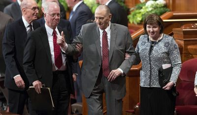 FILE - In this April 1, 2017, file photo, Thomas S. Monson, president of the Church of Jesus Christ of Latter-day Saints, walks with his daughter, Ann Dibb, right, as he leaves the morning session of the two-day Mormon church conference in Salt Lake City. Mormon officials said Monson is no longer coming to meetings at church offices regularly because of limitations related to his age. Eric Hawkins, a spokesman for The Church of Jesus Christ of Latter-day Saints, said Tuesday, May 23, 2017, in a statement that Monson communicates with fellow leaders on matters as needed. (Scott G Winterton/Deseret News via AP, File)