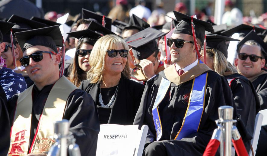 In this Saturday, May 20, 2017 photo, provided by Chapman University, Judy O'Connor, center, sits with her son, MBA graduate Marty O'Connor, during commencement at Chapman University in Orange, Calif. Chapman University gave a surprise honorary degree to Judy O'Connor, mother of Marty O'Connor a quadriplegic student after she attended every class and took notes for him while he earned a master's degree. (Chapman University via AP)