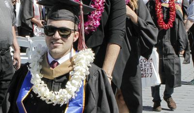 In this Saturday, May 20, 2017 photo, provided by Chapman University, Judy O'Connor pushes her son, MBA graduate Marty O'Connor during commencement at Chapman University in Orange, Calif. Chapman University gave a surprise honorary degree to Judy O'Connor, mother of Marty O'Connor a quadriplegic student after she attended every class and took notes for him while he earned a master's degree. (Chapman University via AP)