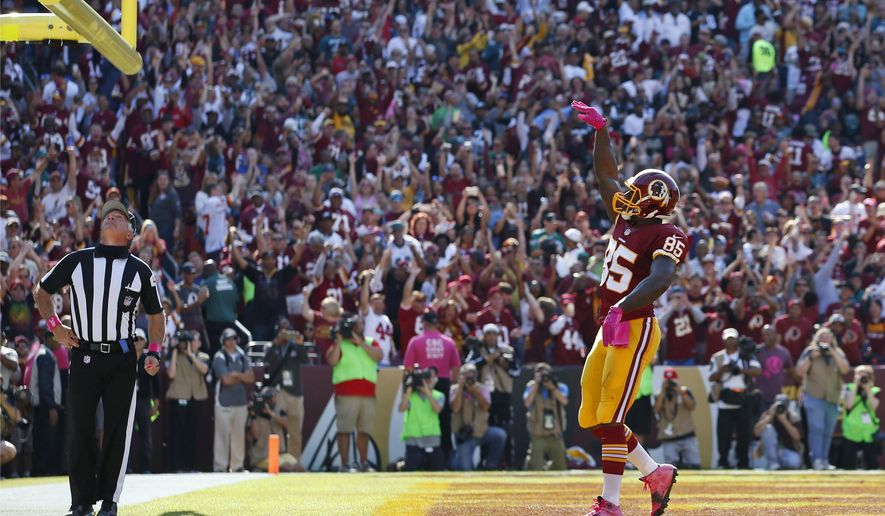 FILE - In this Oct. 16, 2016, file photo, Washington Redskins tight end Vernon Davis tosses the football through the goal posts to celebrate scoring a touchdown in the first half of an NFL football game against the Philadelphia Eagles in Landover, Md. The NFL wants to put some flair back into celebrations, allowing players to use the football as a prop, celebrate as a group and roll around on the ground again if they choose. (AP Photo/Alex Brandon, File)
