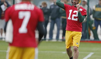 Green Bay Packers quarterback Aaron Rodgers throws passes with quarterback Brett Hundley during NFL football practice Tuesday May 23, 2017, in Green Bay, Wis. (AP Photo/Matt Ludtke)