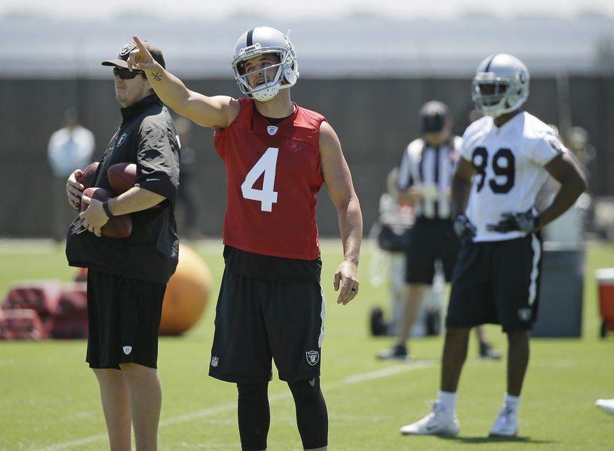 Oakland Raiders quarterback Derek Carr (4) gestures as wide receiver Amari Cooper, right looks on during an NFL football team activity Tuesday, May 23, 2017, in Alameda, Calif. (AP Photo/Eric Risberg)