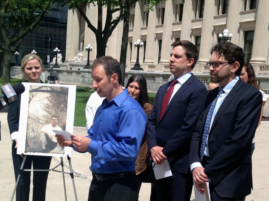 """James Todero reads a statement on Tuesday, May 23, 2017, in downtown Indianapolis near a photograph of his late brother, Charles """"Charlie"""" Todero, during a news conference with the family's attorneys about a federal lawsuit filed over Charles Todero's death last year. The lawsuit alleges Todero's constitutional rights were violated in what it calls an unprovoked """"brutal and deadly assault"""" in which an officer used a Taser on the 30-year-old man in Greenwood, just south of Indianapolis. (AP Photo/Rick Callahan)"""