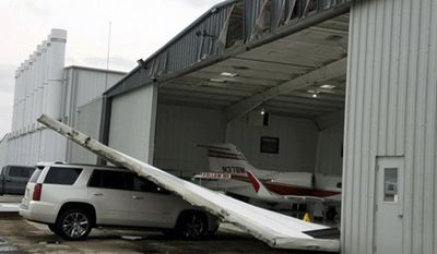 In this Tuesday, May 23, 2017, photo provided by the City of Denton, Texas, part of a damaged hangar is shown sitting atop a vehicle after severed weather passed through the area overnight at the Denton Enterprise Airport.(AP Photo/ City of Denton, Lindsey N. Baker)