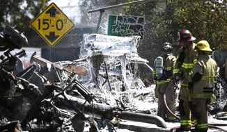 Fire crews work the scene of a large fire involving a big rig Tuesday, May 23, 2017, in the area of Highway 99 and Applegate Road in Atwater, Calif. (Andrew Kuhn /The Merced Sun-Star via AP)