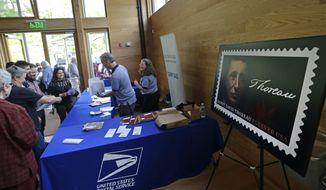 People line up to buy stamps after the dedication of the U.S. Postal Service's new Henry David Thoreau postage stamp, Tuesday, May 23, 2017, at Walden Pond in Concord, Mass. where the 19th century American philosopher and naturalist spent two years in solitude and reflection. (AP Photo/Elise Amendola)