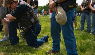 At left, Paul Kocic, who served in the U.S. Army from 1973-1998, bows his head during a moment of silence for fallen troops at the Rolling Thunder program near the National Mall during the Memorial Day weekend, in Washington, D.C., Sunday, May 29, 2011. The Rolling Thunder organization's mission is to bring awareness to the POW-MIA issue and to educate the public about how many American prisoners of war were left behind after all past wars. (Drew Angerer/The Washington Times)